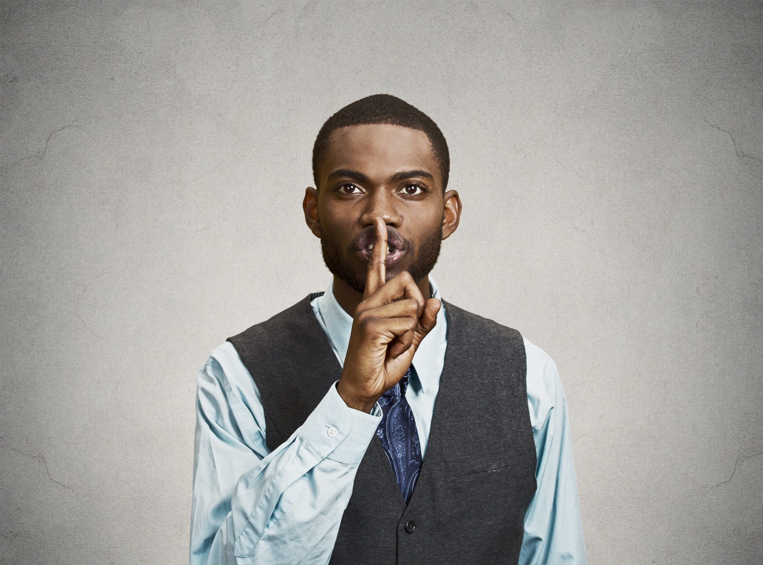 A man places a finger to his lips to let someone know they shouldn't share sensitive information. A lawyer and his legal insurance could tell him that a non-disclosure agreement would get the job done right.